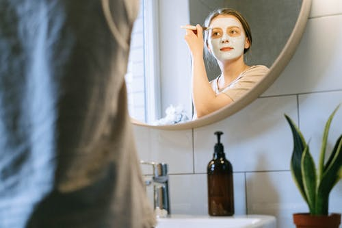 A woman standing in front of a mirror posing for the camera